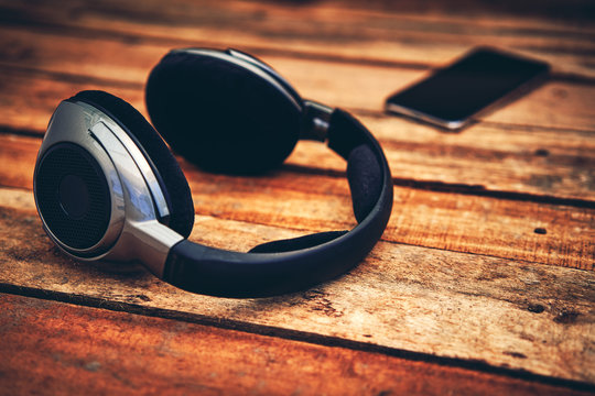 A 45 degree view of a set of wireless headphones and mobile phone lying on a rustic wooden table outside. Styling and grain effect added to image.
