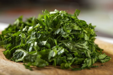 Close up of fresh green chopped parsley on wood