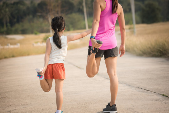 mother and her daughter doing stretching exercises on the road in the countryside, sports, healthy lifestyle