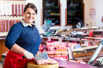 Butcher woman chopping meat on a block with big knife
