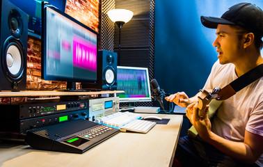 asian male guitarist recording electric guitar track in home studio