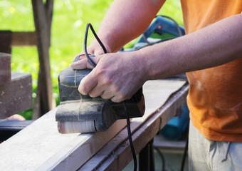 Handyman using electric sander machine outdoors.