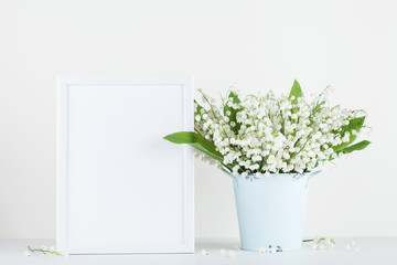 Mockup of picture frame decorated flowers in vase on white background with clean space.