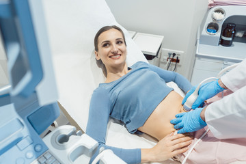Woman and doctor looking at ultrasonic screen during examination being happy as she is pregnant