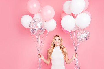 Portrait of trendy cheerful elegant girlfriend having many white air balloons in two hands looking up enjoying ballons isolated on pink background