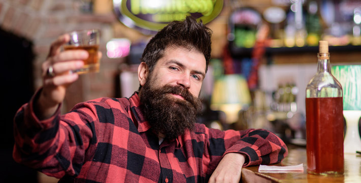 Guy spend leisure in bar, defocused background. Hipster with beard holds alcoholic beverage. Cheers concept. Man drinks whiskey or cognac. Man on relaxed face sits near bar counter, raising up glass.