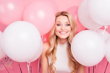 Wall Mural - Portrait of cheerful childish girl with many white air balloons around looking at camera isolated on pink background