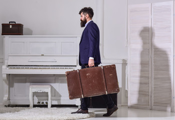 Macho stylish on strict face walks and carries big vintage suitcase, side view. Baggage and travelling concept. Man, traveller with beard and mustache with baggage, luxury white interior background.