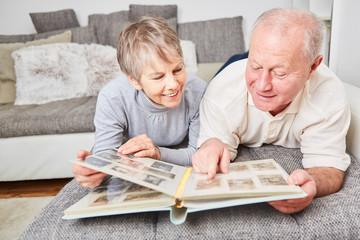 Senioren Paar betrachtet Fotos im Fotoalbum