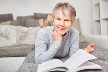 Seniorin mit einem Buch auf der Couch