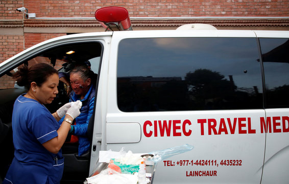 Xia Boyu, a Chinese double amputee climber, who lost both of his legs during his first attempt to climb Everest, is checked by a doctor while sitting in an ambulance upon his arrival, after successfully climbing Mount Everest, in Kathmandu