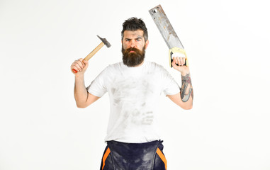 Man with serious face holds saw and hammer. Handyman concept.