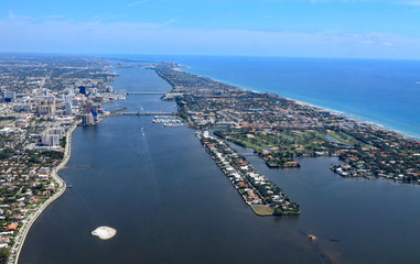 Aerial view downtown West Palm Beach, Florida, and the island of Palm Beach, with the Lake Worth Lagoon separating the two.