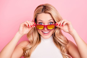 Portrait of cheerful positive girlfriend with shocked surprised impressed reaction looking out glasses on her face at camera holding eyelets with two hands isolated on pink background