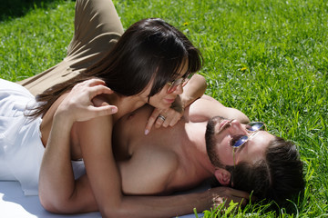 A girl in a white dress and a bearded man with a naked torso hugging lie on the grass. The models in sunglasses.