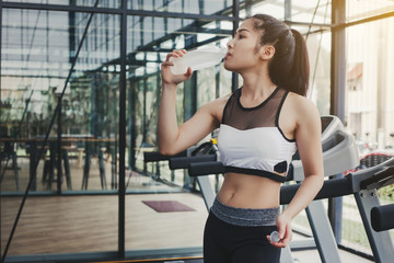 Woman drinking water after workout exercising in the gym