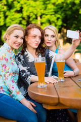 Happy friends taking selfie with smartphone in beer garden