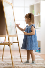 Child girl drawing on white board at home
