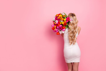 Rear view portrait with copy space empty place of pretty tempting woman in white elegant dress with booty fit butt holding big bouquet of tulips on shoulder isolated on pink background