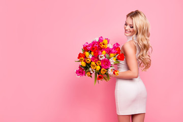 Full size portrait with copyspace empty place of tempting slim seductive girlfriend with booty bum holding big bouquet of tulips in hands looking at flowers isolated on pink background