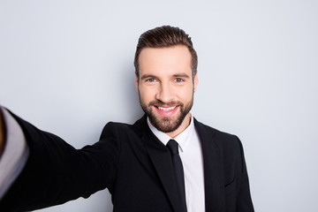 Self portrait of creative trendy man shooting selfie on smart phone with arm, looking at camera, isolated on grey background, having video-chat with partners friends