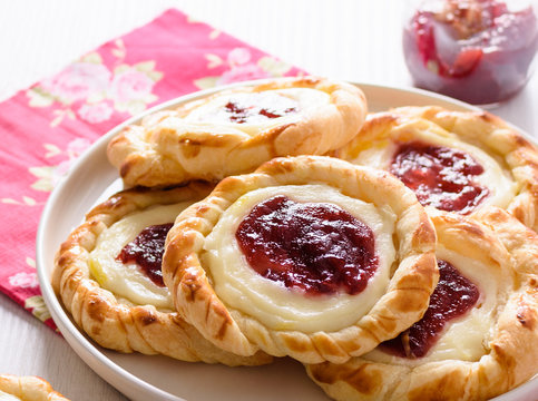 Danish pastries for breakfast on a wooden table. Pastries are stuffed with cheese cream and cranberries jam.