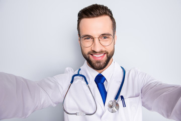 Self portrait of joyful cheerful doc in white outfit with tie and stubble having stethoscope on his neck shooting selfie with two arms, isolated over grey background
