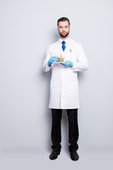 Full size fullbody portrait of attractive stylish  scientist in white lab coat, black pants, blue tie holding test tubes with multi-colored liquid, looking at camera, isolated on grey background