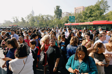 People stand outside a building after a tremor was felt in Mexico City