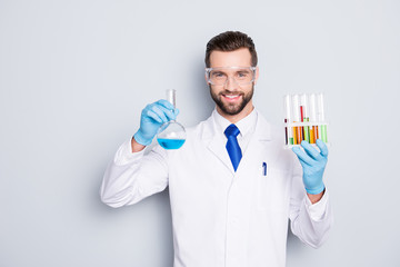 Portrait of cheerful handsome scientist with bristle in white lab coat, tie, protective glasses having test tubes and flask with multi-colored liquid, looking at camera over grey background