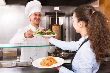 Happy waitress receiving order from chef