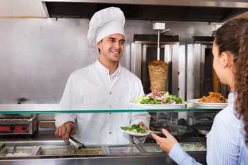 Happy  male worker serving customer with smile at shawarma place