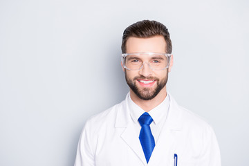 Portrait of stylish positive scientist with hairstyle in white outfit with tie in protective glasses looking at camera isolated on grey background