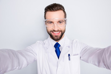 Self-portrait of cheerful positive man with stubble in white outfit with tie shooting selfie with two arms, isolated on grey background, having fun, leisure, rest, relax, video-call