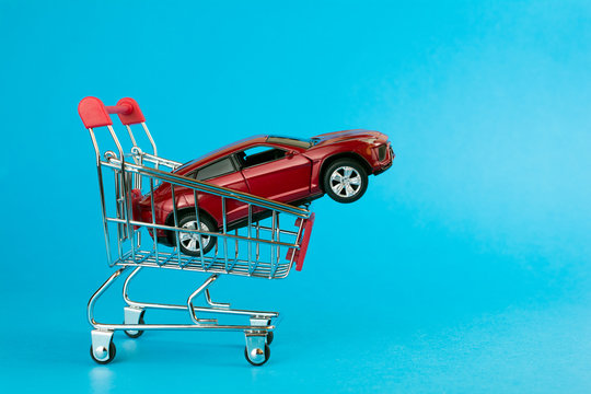 car loan concept. red car shopping cart blue background