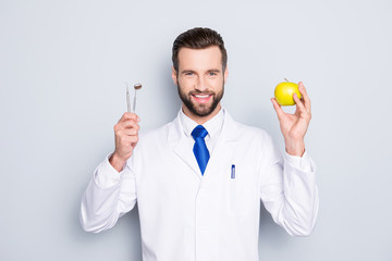 Portrait of successful toothy dentist in white lab coat, blue tie, holding equipments and green apple in hands, isolated on grey background, recommend taking care about teeth