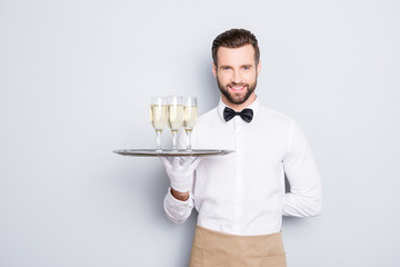 Portrait of joyful friendly man in white classic shirt and black bow holding hand behind the back and tray with three glasses of sparkling wine, isolated on grey background, looking at camera