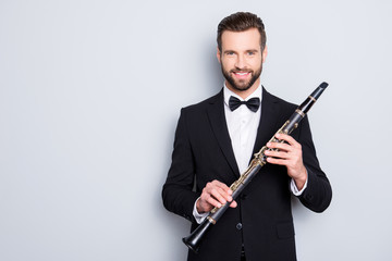 Portrait with copyspace, empty place of stylish cheerful man with hairstyle in black tux holding bassoon in hands, looking ta camera, isolated on grey background