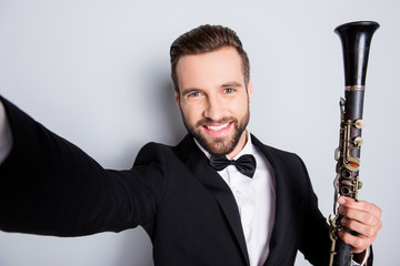 Self portrait of creative cheerful man in tux shooting selfie on front camera with arm, having showing bassoon, isolated on grey background, having rest relax leisure fun video-call
