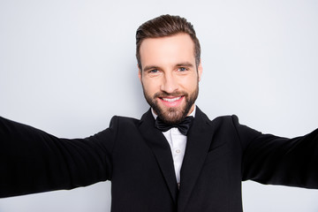 Self portrait of stylish cheerful artist in black suit with bowtie, shooting selfie on front camera of smart phone with two arms, having video-call, isolated on grey background