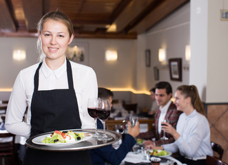 Smiling waitress with serving tray