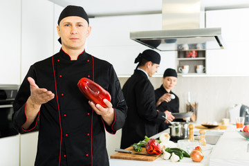 Professional chef  in black uniform standing  with big red  pepper