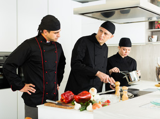 Professional chefs  in black uniform  working with vegetables