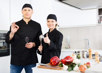 Man and woman young cooks in uniform showing thumbs up