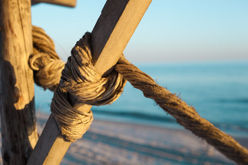 A braided rope is wrapped in a wooden canopy on a sandy beach in the sunlight