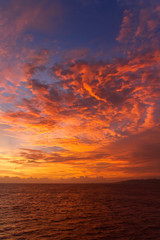 summer sunset colorful sky with dramatic  purple red and yellow clouds over picturesque water landscape. Bali, Indonesia.