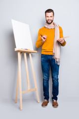 Full size body portrait of joyful trendy artist with scarf around neck, hairstyle, in jeans, sweater, holding colorful palette and brushes in hands, isolated on grey background
