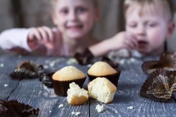 Children taste finished cupcakes sitting behind wooden surface