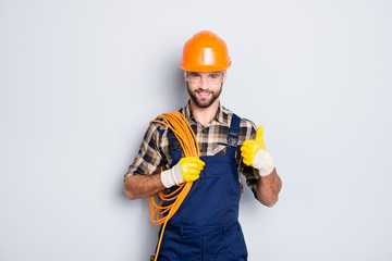 Portrait of handsome joyful electrician in hardhat, overall, shirt with bristle, holding rolled wires on shoulder, showing thumb up recommend approve sign over grey background