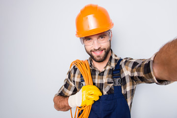 Self portrait of attractive joyful man in hardhat, overall, shirt, holding rolled cable on shoulder, blogger shooting selfie on front camera, isolated on grey background, having leisure